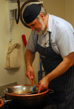 Master Chocolatier, Leopold Schreiber, stirring chocolate in copper kettle